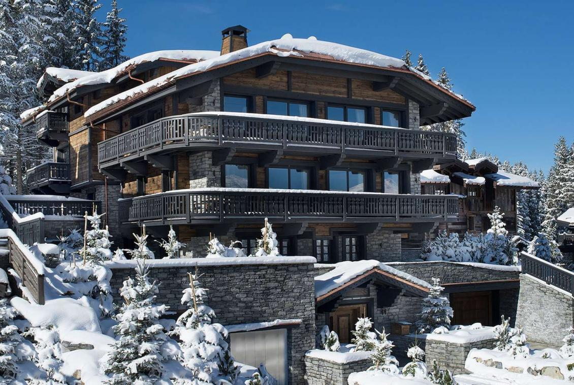 kings-avenue-luxury-chalet-courchevel-001-front-view-exterior-snow-with-blue-sky