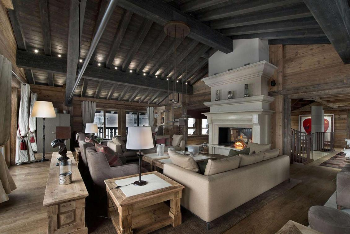 kings-avenue-luxury-chalet-courchevel-001-living-room-with-open-fireplace-front-view