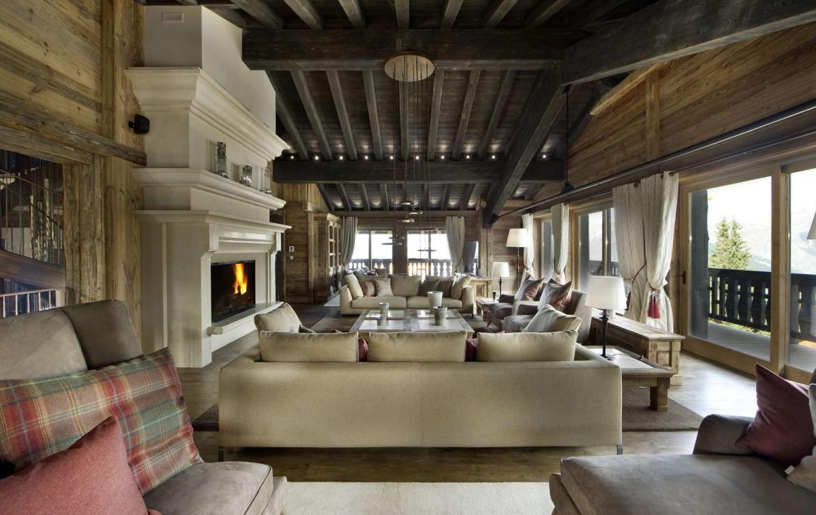 kings-avenue-luxury-chalet-courchevel-001-living-room-with-open-fireplace-side-view