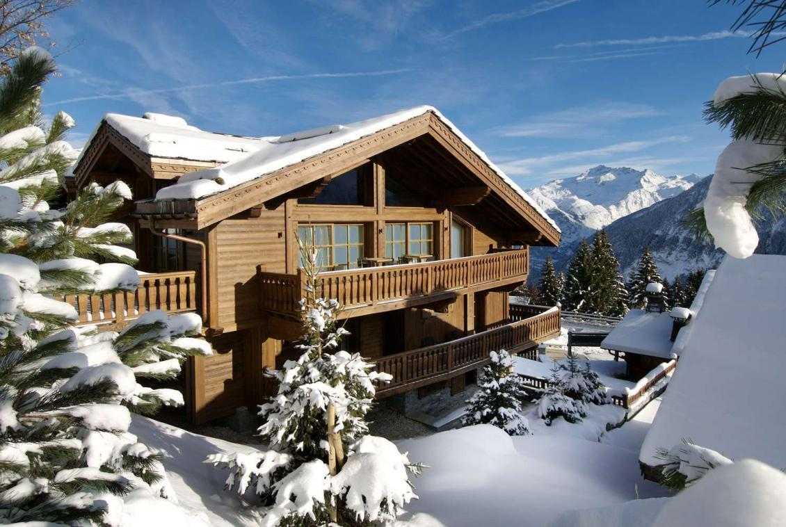 kings-avenue-luxury-chalet-courchevel-004-front-view-exterior-with-snow-and-blue-sky