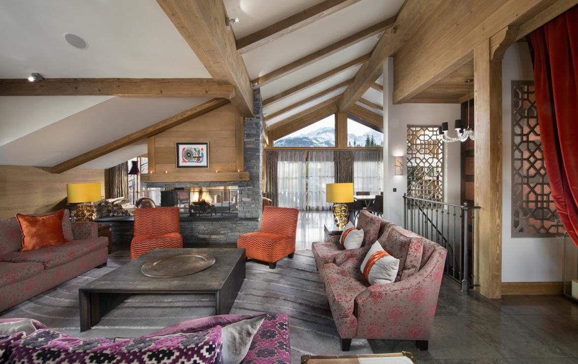 kings-avenue-luxury-chalet-courchevel-004-living-area-with-open-fireplace