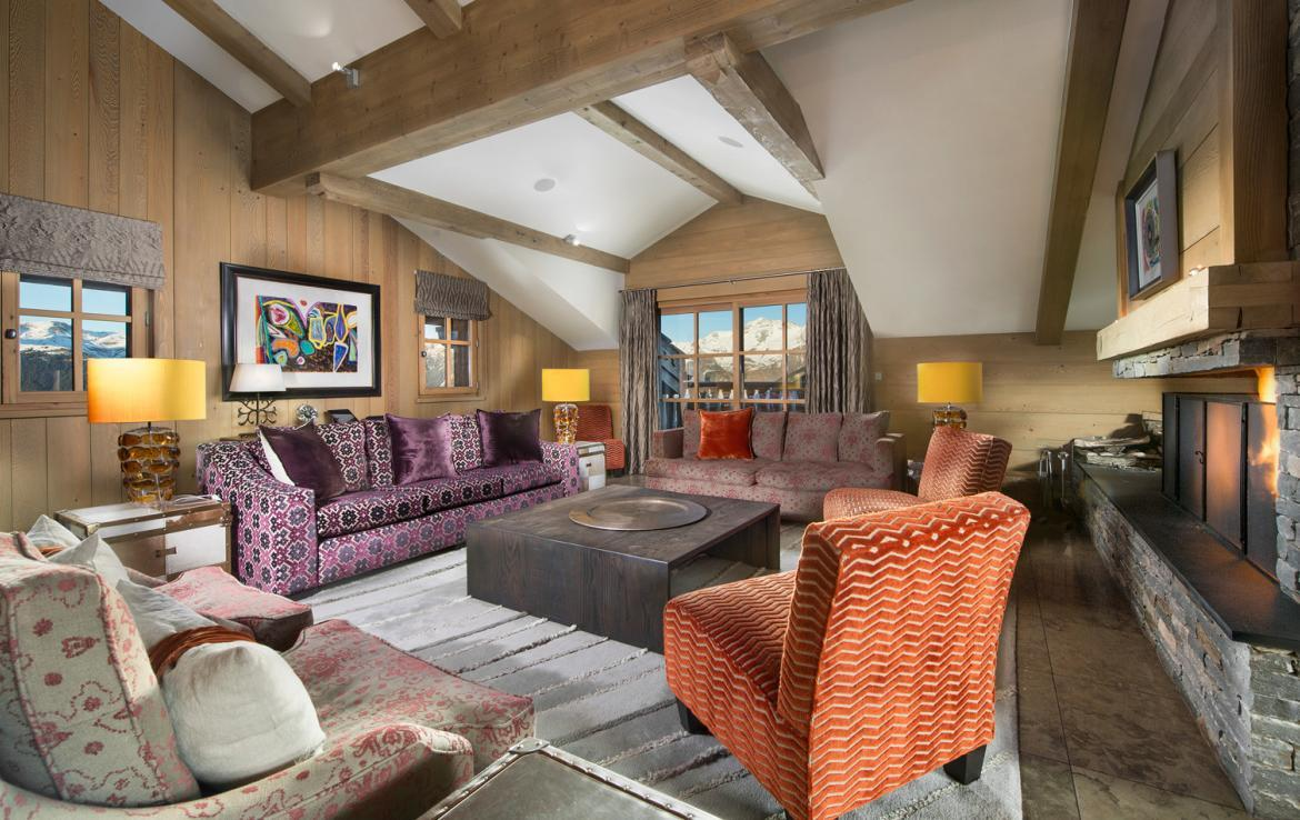 kings-avenue-luxury-chalet-courchevel-004-side-view-living-area-with-open-fireplace-and-mountain-views