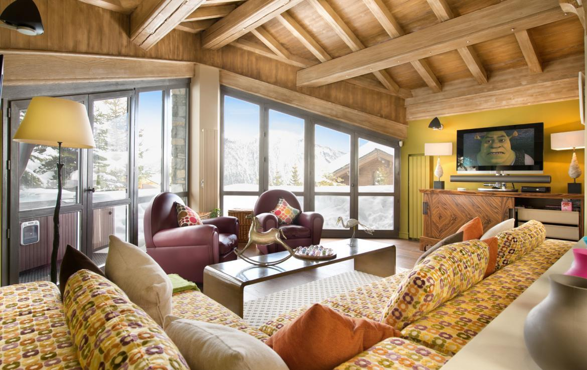 kings-avenue-luxury-chalet-courchevel-006-relaxation-area-with-tv-big-windows-and-mountain-views