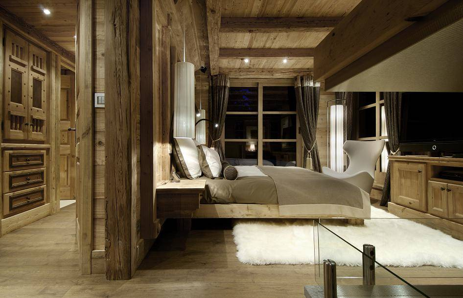 kings-avenue-luxury-chalet-courchevel-010-wooden-master-bedroom-with-tv-and-balcony